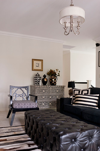 Black leather ottoman, sofa and chest of drawers with mother-of-pearl marquetry in living room