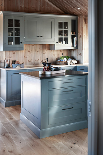Blue-grey kitchen with island counter in cottage with wooden walls and gable roof