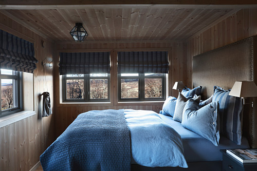 Bedroom with wooden walls and low ceiling in cottage