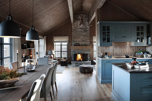 Fireplace, dining table and kitchen area in cottage interior