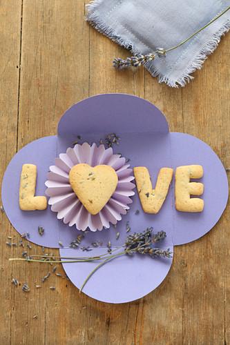 Letter-shaped lavender biscuits spelling 'Love' on handcrafted, purple paper envelope