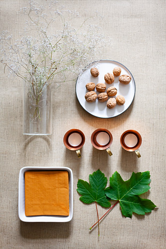 Napkins in bowl, vine leaves, tealights, walnuts and flowering twigs in glass vase
