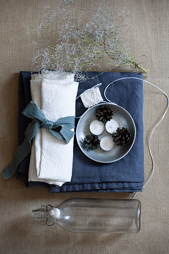 White linen napkin with blue ribbon, tealights, pine cones, yarn, flowering twigs and swing-top bottle