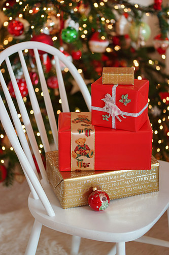 Festively wrapped Christmas presents on white chair