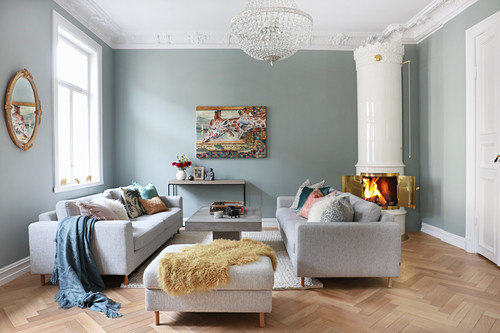 Sofa set, coffee table and Swedish tiled stove in living room with herringbone parquet floor