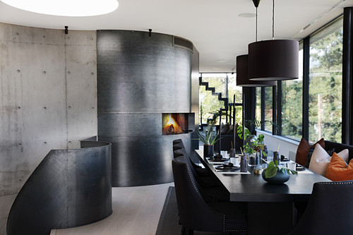 Set dining table in black, open-plan interior with fireplace