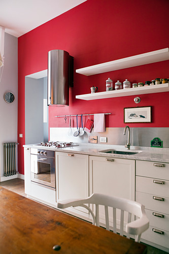 White kitchen counter with modern stainless steel extractor hood against red-painted wall