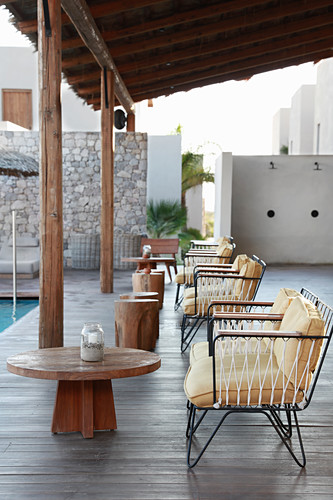 Lounge furniture on roofed terrace next to pool