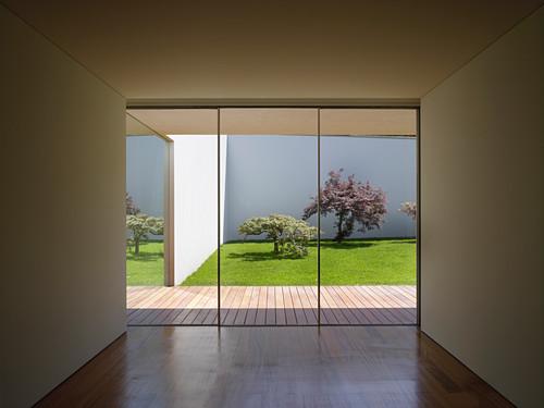 Blick aus kubisch minimalistem Raum durch Fensterfront auf Holzterrasse und Patio