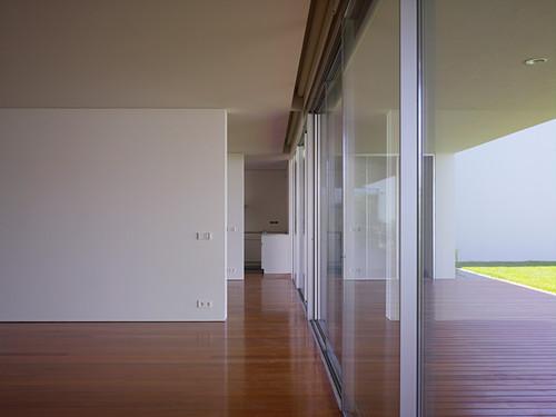 Durchgang entlang Trennwänden und Fensterfront in minimalistischem Wohnhaus