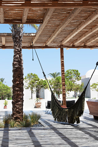 Hammock on terrace with thatched sun shade
