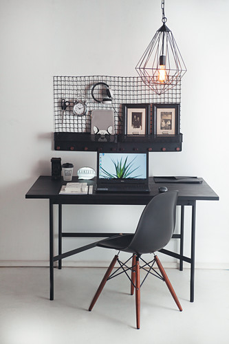 Black table and designer chair below wall-mounted organiser in work area