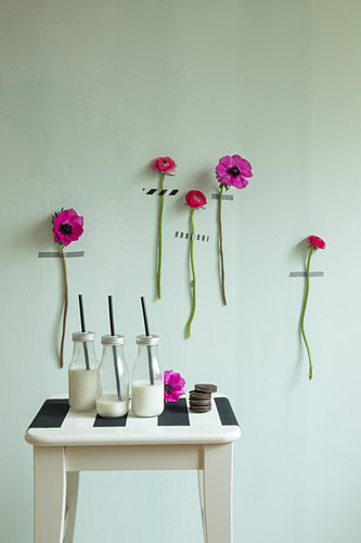 Hot-pink flowers with stems stuck on green wall and bottles of milk on stool