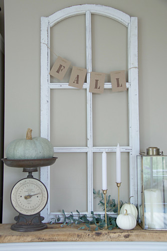 Ornamental window frame, ornamental squash on vintage kitchen scales, and candles on mantelpiece