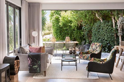 Exotisches Wohnzimmer mit offener Fensterfront zu Terrasse und Garten