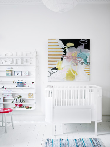 Abstract painting above cot in white nursery