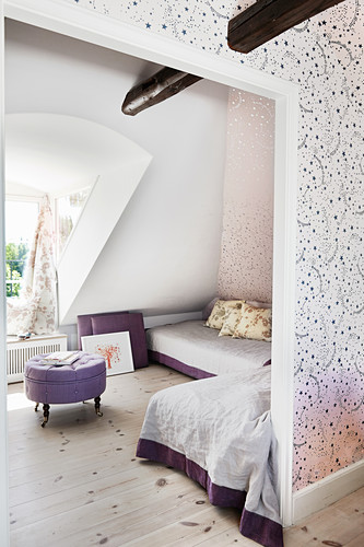 Child's bedroom consisting of two rooms with star-patterned wallpaper and sloping attic walls