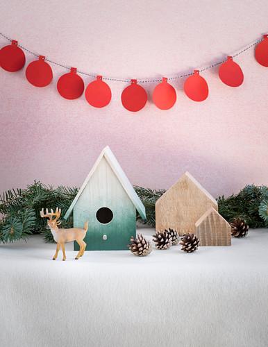 Winter arrangement of nesting box, fir cones, reindeer figurine and garland