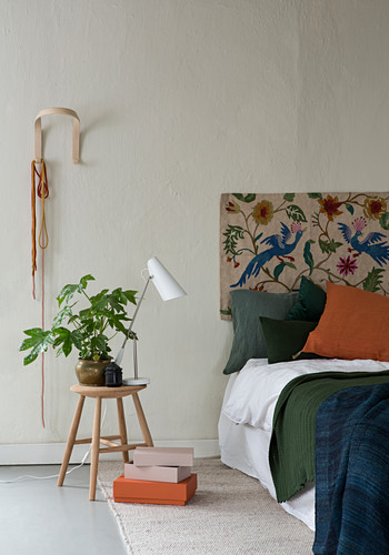 Fatsia japonica on stool used as bedside table next to bed