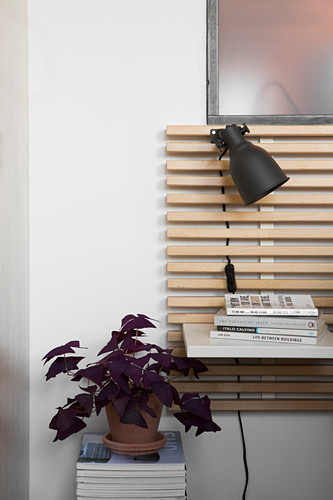 Potted red oxalis on stacked books next to bed headboard with integrated shelf