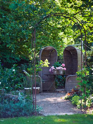 High-backed wicker armchairs on small gravel terrace hidden amongst trees in garden