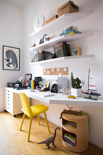 White desk top, white shelves and yellow chair in teenager's bedroom