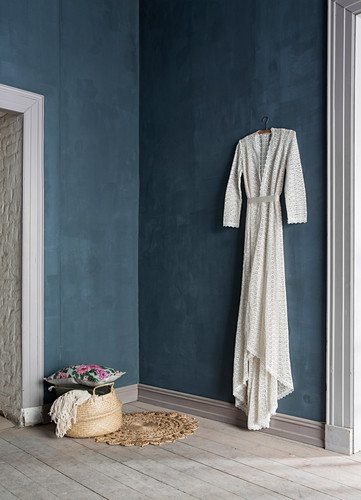 White vintage dress hung on dark blue wall in period building