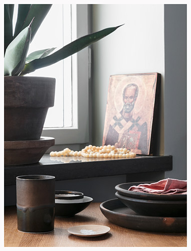 Rustic earthenware crockery on table in front of window