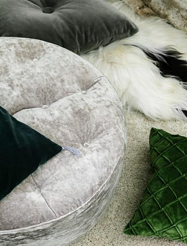 Velvet cushions in grey and green on fur blanket on rug