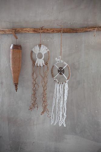 Rustikale Traumfänger an einem Ast vor grauer Wand