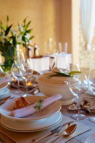 Mediterran gedeckter Tisch mit weißem Geschirr und Silberbesteck