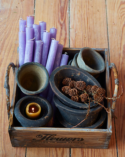 Lilafarbene Kerzen und rustikale Pflanztöpfe in alter Holzkiste