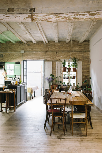 Vintage wooden table and chairs in restaurant with rustic ceiling and potted houseplants on shelves in window