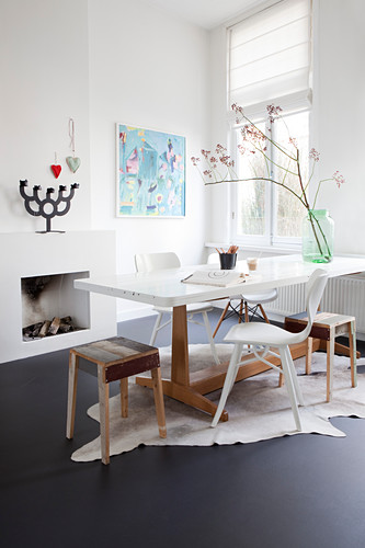 Various chairs and stools made from reclaimed wood around dining table on cowhide rug