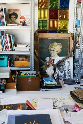 Antlers, paintings and knick-knacks between two sets of shelves