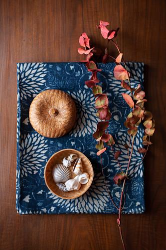 Herbstlicher Eukalyptuszweig, Korb mit Muscheln auf blauem Stoff