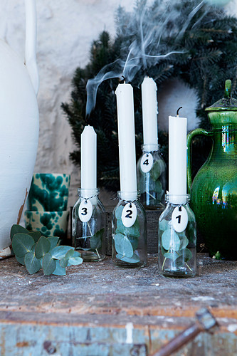 Advent arrangement of white candles in glass bottles