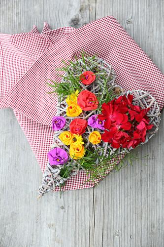 Dekoherz aus Weidengeflecht mit echten Geranien und bunten Papierblüten auf kariertem Tuch