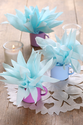 Handmade table decorations made from napkin flowers in coloured enamel cups