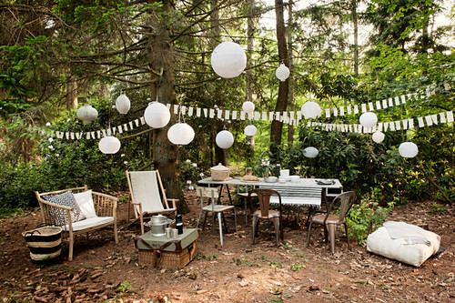 Table and chairs and further seating amongst party decorations in woodland clearing