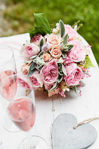 Lavish bouquet of roses, lily-of-the-valley and lamb's ear, glasses of pink Champagne and heart pendant