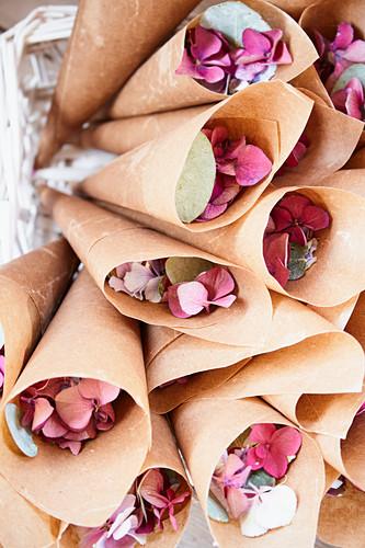 Hydrangea-petal confetti in paper cones