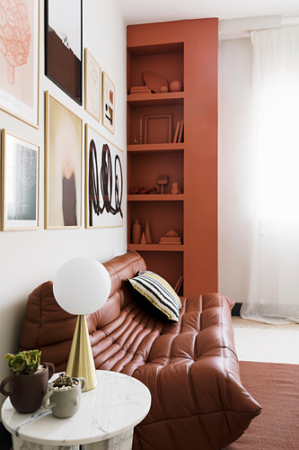 Brown, modern, leather sofa below gallery of pictures and next to shelves