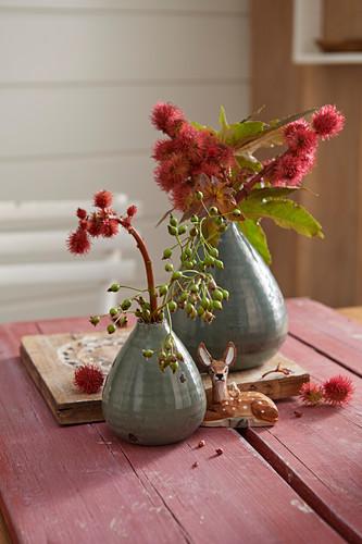 Zweige mit roten Blüten in Vasen und Rehfigur