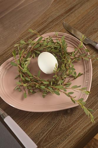 Ei in einem Kranz aus Zweigen auf herzförmigem Teller in Rosa