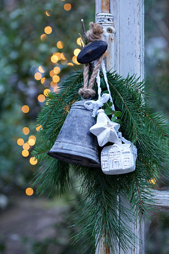 Arrangement of fir branches, bell, star and small house hung from window handle
