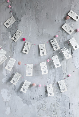 DIY garlands made from book pages with punched heart motifs and pompoms