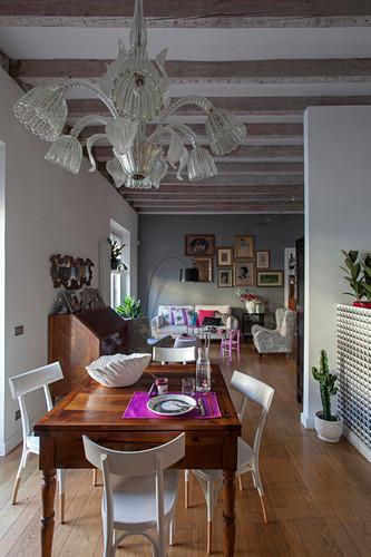Blick vom Esstisch mit antikem Kronleuchter ins offene Wohnzimmer