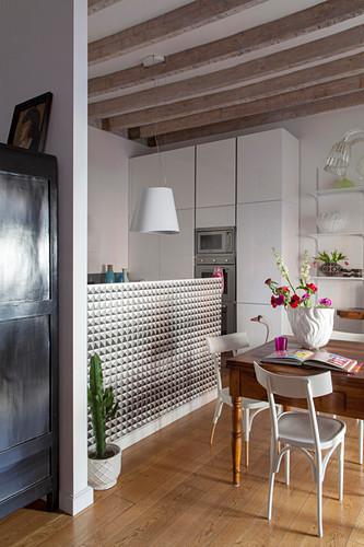 Alter Holztisch vor moderner weißer Küche im offenen Wohnraum