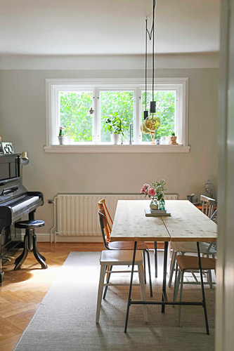 Various chairs around dining table in front of window